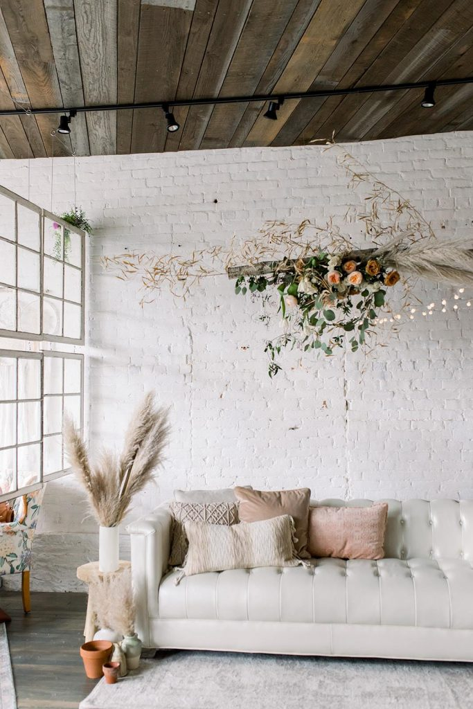 white couch by white wall with wedding flowers