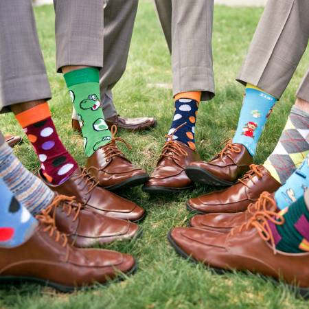 wedding party holding pant leg up to show colored socks