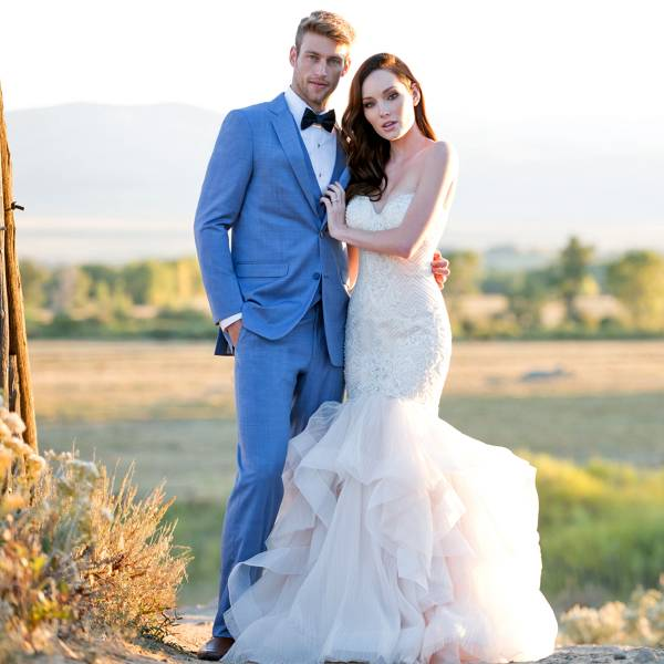 Bride and groom posing in field in blue tuxedo and white dress